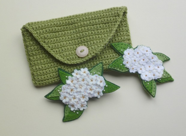 a crochet purse with both elderflower brooches